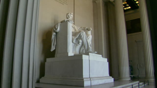 MS POV Shot of behind interior columns approaching Abraham Lincoln sitting in chair statue and Worms Eye View statue at Lincoln Memorial / Washington, District of Columbia, United States