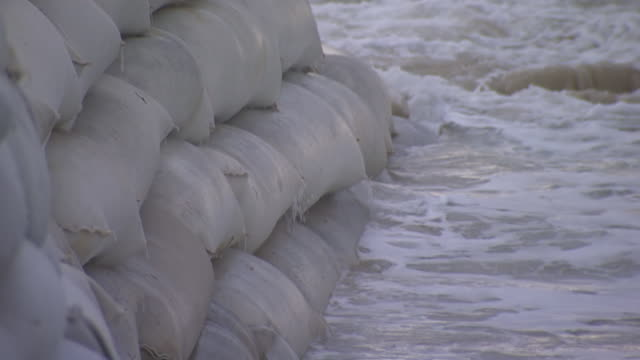 CU Shot of Big waves splashing on sandbag wall / Kingscliff, New South Wales, Australia