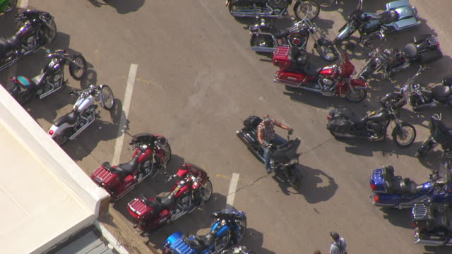 MS AERIAL TS Shot of bikers driving past parked motorcycles on Main Street / Sturgis, South Dakota, United States