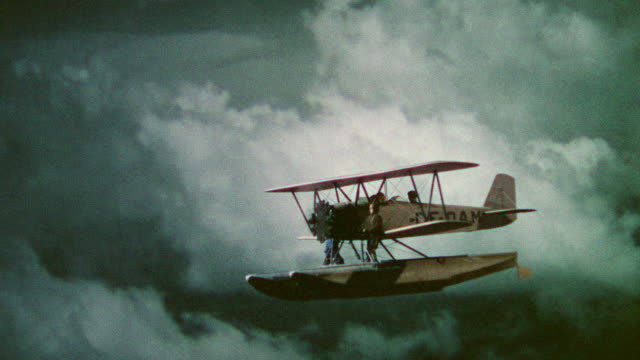 MS Shot of biplane flying through cloudy sky with man standing near front of plane (miniature)