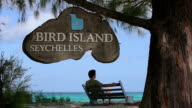 MS Shot of Bird Island Sign with man on bench / Bird Island, Seychelles