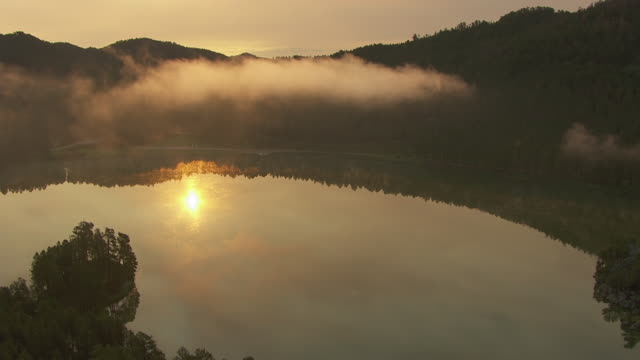 MS AERIAL Shot of Bismark Lake in Custer County as sun is rising with cloud hovering in sky / South Dakota, United States