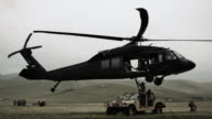 Shot of Black Hawk helicopter attaching and hauling off Humvee from field.