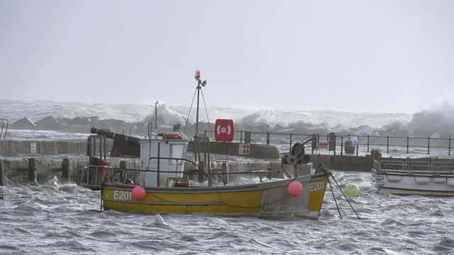 MS SLO MO Shot of Boat anchored in Cobb at Lyme Regis shows violent sea beyond sea wall / Newcastle Emlyn, Ceredigion, United Kingdom
