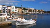 WS Shot of boats at small harbour near houses / Portocolom, Mallorca, Balearic Islands, Spain