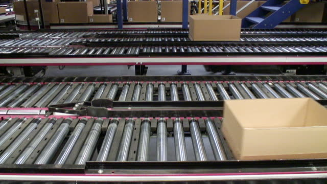 MS Shot of Box moving on conveyer belts in warehouse / Hamburg, Germany