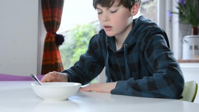 MS Shot of boy in kitchen disinteresting in food / London, Greater London, United Kingdom