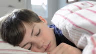 CU Shot of boy looking tired in bed / London, Greater London, United Kingdom