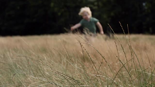MS PAN SLO MO Shot of boy playing through grass field