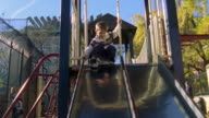 MS TS Shot of Boy sliding down from slide in park / New York, United States