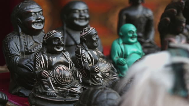 MS Shot of Buddha figurines sit on table for sale at Merchant shop in Namche Bazarre / Namche, Nepal