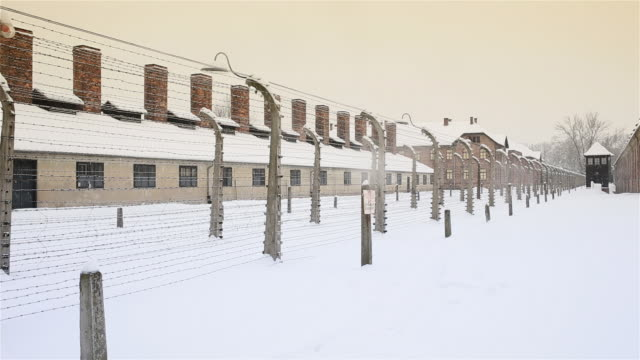 MS Shot of Building behind barbed wire fence at Auschwitz with snow rain / Auschwitz-Birkenau, Krakow, Poland
