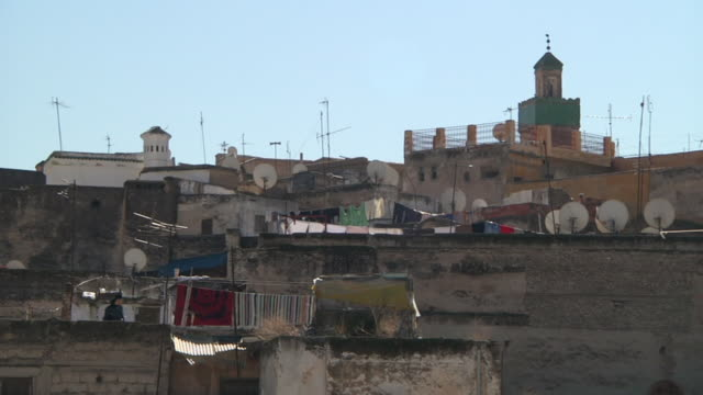 MS Shot of building stacking each other with cable dishes on top and rugs hanging out to dry / Fes, Centro-North, Morocco
