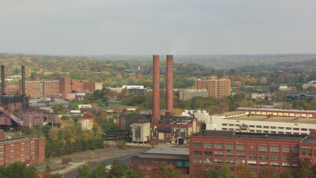 WS TU TD ZI AERIAL Shot of buildings and BF Goodrich factory smokestacks / Akron, Ohio, United States