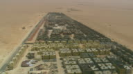 MS AERIAL Shot of buildings construction site at open land in city / Qatar
