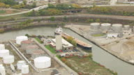 WS AERIAL Shot of bulk carrier Calumet in Cuyahoga River near oil tank farm / Cleveland, Ohio, United States