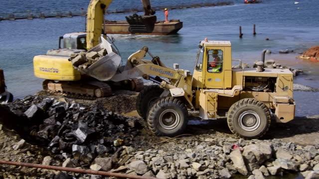 MS TC PAN Shot of Bulldozer dumping soil on harbour edge.Luanda, Angola / Luanda, Angola