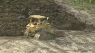 MS AERIAL Shot of bulldozer moving large amounts of dirt ground / Louisiana, United States