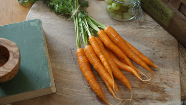 CU PAN SLO MO Shot of bunch of carrots being laid on to cutting board / United Kingdom