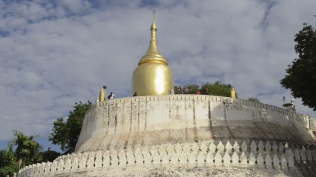 MS LA Shot of Bupaya temple with golden stupa at Ayeyarwady river with people / Bagan, Mandalay Division, Myanmar