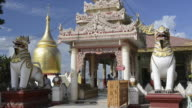 CU Shot of Burmese men leave Bupaya temple with two lion (Chinthe) as temple guard and golden stupa at Ayeyarwady river / Bagan, Mandalay Division, Myanmar