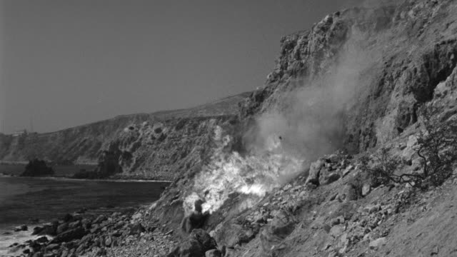 MS Shot of burning car falling over cliff