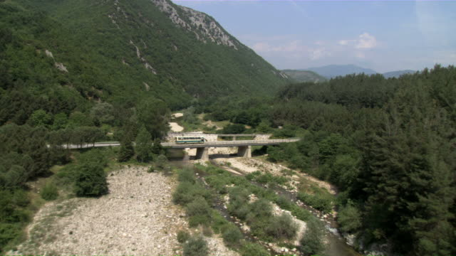 WS AERIAL Shot of bus passing on small bridge over river in forest / Thraki, Thrace, Greece