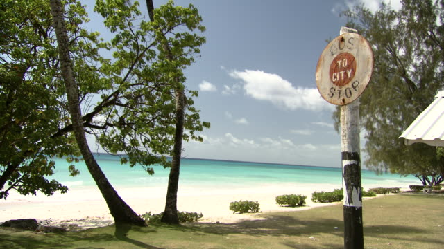 MS Shot of Bus stop sign with blue sea and beach / Bridgetown, Saint Michael, Barbados