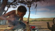 MS LA Shot of Bush person making object out of wood, Boesmanland / North West Province, South Africa
