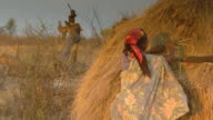 MS Shot of bush woman grabbing straw and placing it on roof of hut / Limpopo, South Africa
