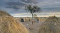 WS Shot of bushman village life child runs between huts / Limpopo, South Africa