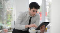 MS Shot of business man in kitchen eating breakfast and looking at digital tablet / London, Greater London, United Kingdom