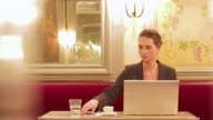 MS Shot of Businesswoman in cafe working on laptop using phone and ordering more coffee / Toulouse, Haute Garonne, France