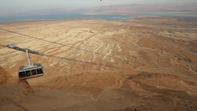 WS PAN Shot of cable car going down Masada with dead sea in Negev desert / Israel