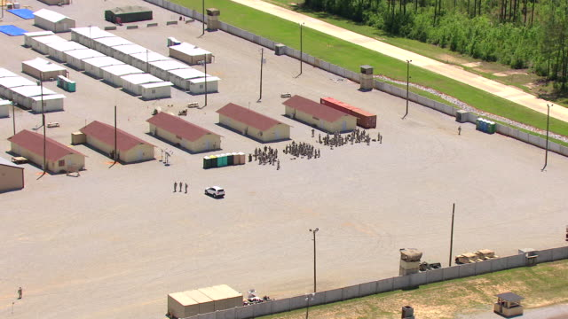 MS AERIAL ZI Shot of campus and soldiers standing around with gear at Camp Shelby military post / Mississippi, United States