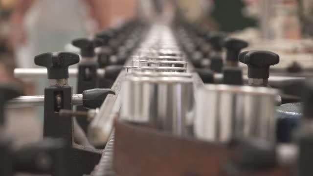 MS R/F Shot of canned macadamia nuts rolling through conveyor belt / kauai, hawaii, united states