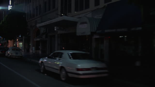MS POV Shot of car and shops at sidewalk in city at night