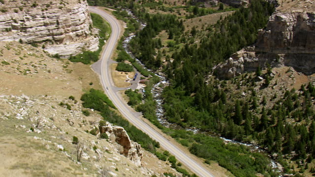WS AERIAL Shot of cars running on road parallel with trees and flowing river / Wyoming, United States