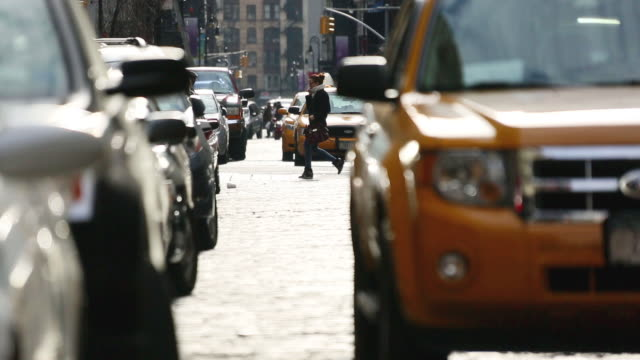 MS Shot of cars running on shining Stone pavement street at SOHO with Cars and pedestrians crosses street / New York, United States