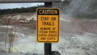 MS Shot of caution sign at Sulphur Banks with steam and suplur banks in distance in Volcanoes National Park / Volcano, Hawall, Big Island, United States