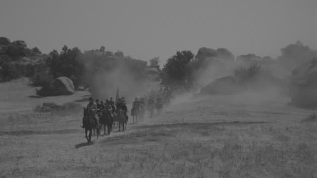 WS Shot of cavalry on horseback with wagon moving through open landscape