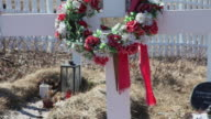 CU Shot of Cemetary with artificial flowers and red ribbon on wreath moving in wind / Sisimiut, Qeqqata, Greenland
