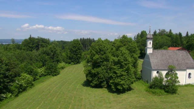MS POV AERIAL Shot of chapel in forest clearing / Wolfratshausen, Bavaria, Germany