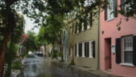 MS Shot of Charleston South Carolina Tradd Street with wet street and old homes with color and flowers doorways / Charleston, South Carolina, United States