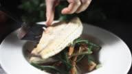 CU PAN SLO MO Shot of chef adding garnish to fish dish / United Kingdom