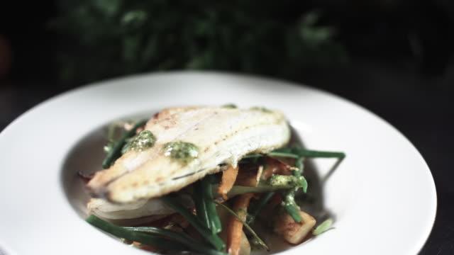 CU R/F SLO MO Shot of chef adding garnish to fish dish / United Kingdom
