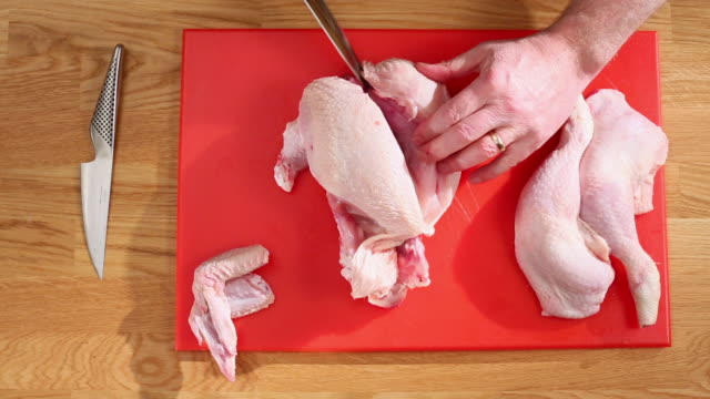 MS Shot of Chef cutting raw chicken into parts cutting off first breast on red chopping board / Newport, South Wales, United Kingdom