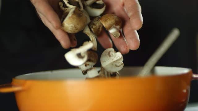 CU R/F SLO MO Shot of chef dropping mushrooms into pan