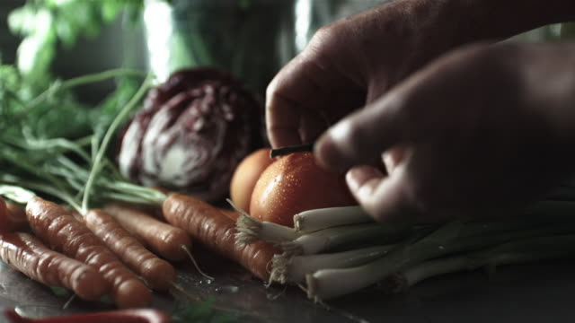 CU R/F SLO MO Shot of chef's hand selecting tomato from collection of vegetables / United Kingdom