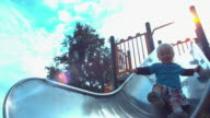 MS SLO MO Shot of child sliding down slide in park
